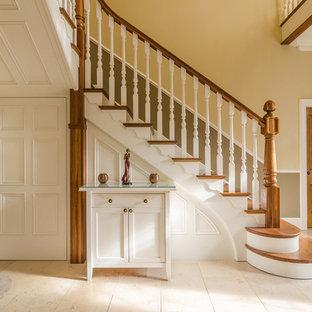 Diseño de escalera en L, tradicional, con escalones de madera y contrahuellas de madera pintada