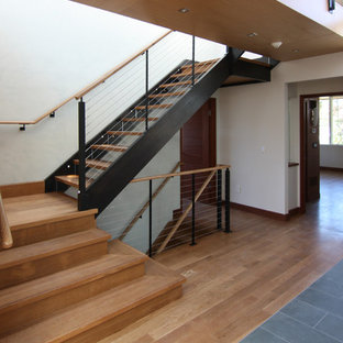 Staircase - large contemporary wooden u-shaped cable railing staircase idea in New York with glass risers
