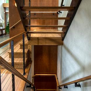 ニューヨークの大きい木のコンテンポラリースタイルのおしゃれな折り返し階段 (ガラスの蹴込み板、ワイヤーの手すり) の写真