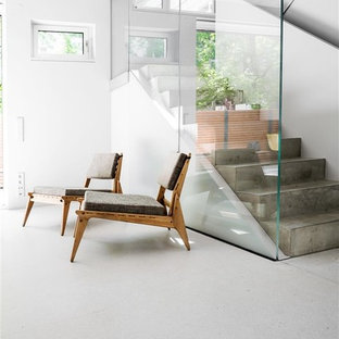 """Ispirazione per una scala a """"U"""" minimalista di medie dimensioni con pedata in cemento, alzata in cemento e parapetto in vetro"""