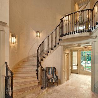 Imagen de escalera curva, mediterránea, grande, con escalones de travertino y contrahuellas de madera pintada