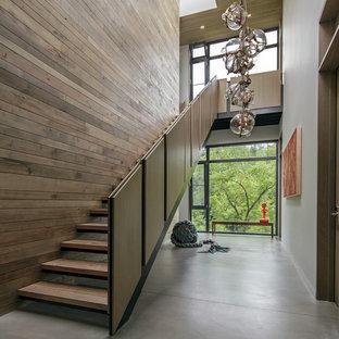 Foto di una grande scala a rampa dritta minimalista con pedata in legno, nessuna alzata e parapetto in materiali misti