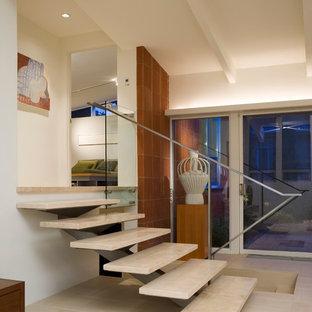 Foto di una scala minimalista con pedata in travertino, nessuna alzata e parapetto in metallo