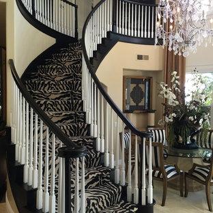 Ejemplo de escalera curva, contemporánea, grande, con escalones enmoquetados, contrahuellas enmoquetadas y barandilla de madera