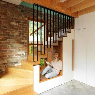 Diseño de escalera suspendida, moderna, pequeña, con escalones de madera, contrahuellas de madera y barandilla de metal