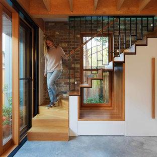 Foto di una piccola scala sospesa moderna con pedata in legno, alzata in legno e parapetto in metallo