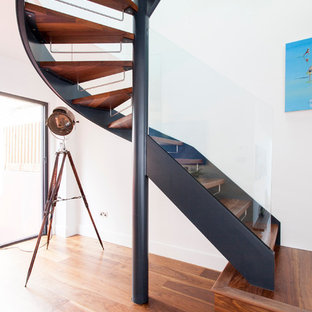 Contemporary wood curved staircase in London with open risers.