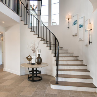 Staircase - large transitional wooden curved metal railing staircase idea in Orange County with marble risers