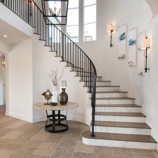 Diseño de escalera curva, clásica renovada, grande, con escalones de madera, contrahuellas de mármol y barandilla de metal