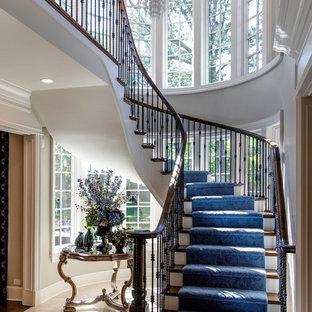 Ejemplo de escalera curva, tradicional renovada, grande, con escalones de madera, contrahuellas de madera y barandilla de metal