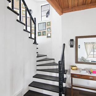 Diseño de escalera curva, tradicional renovada, con escalones de madera pintada, contrahuellas de madera pintada y barandilla de madera