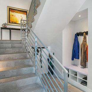 Imagen de escalera curva, actual, de tamaño medio, con escalones con baldosas, contrahuellas con baldosas y/o azulejos y barandilla de metal
