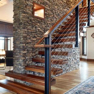 Ispirazione per una scala sospesa minimalista di medie dimensioni con pedata in legno e parapetto in cavi