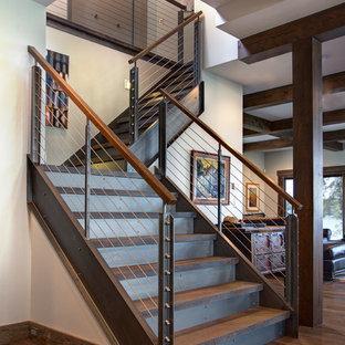 Idée de décoration pour un grand escalier urbain en L avec des marches en bois et des contremarches en métal.