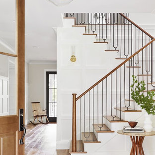 ポートランド(メイン)の木のトランジショナルスタイルのおしゃれな折り返し階段 (フローリングの蹴込み板、混合材の手すり) の写真