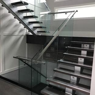 バンクーバーの中サイズの木のモダンスタイルのおしゃれな階段 (ガラスの手すり) の写真