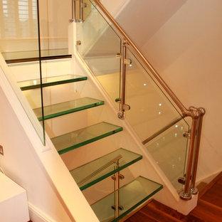 Ejemplo de escalera suspendida, actual, grande, sin contrahuella, con escalones de vidrio