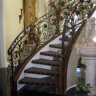 Imagen de escalera curva, clásica, de tamaño medio, sin contrahuella, con escalones enmoquetados