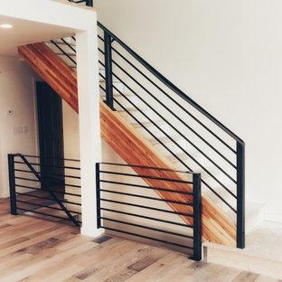 Ejemplo de escalera en L, moderna, de tamaño medio, con barandilla de metal, escalones de madera pintada y contrahuellas de hormigón