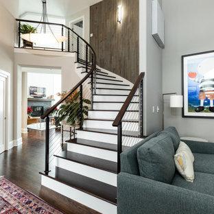 Идея дизайна: изогнутая лестница в современном стиле с деревянными ступенями, крашенными деревянными подступенками и перилами из тросов