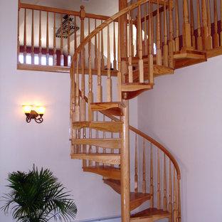 Esempio di una scala a chiocciola classica di medie dimensioni con pedata in legno e alzata in legno