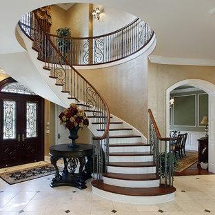 Foto de escalera de caracol, mediterránea, grande, con escalones de madera, contrahuellas de madera pintada y barandilla de metal