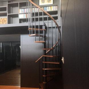 Foto di una piccola scala a chiocciola minimalista con pedata in legno, nessuna alzata e parapetto in metallo