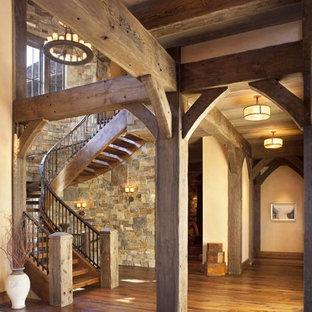 Rustik inredning av en stor svängd trappa i trä, med öppna sättsteg och räcke i metall
