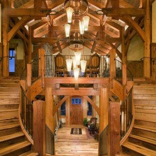 Modelo de escalera curva, rústica, grande, con escalones de madera, contrahuellas de madera y barandilla de metal