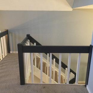 Ejemplo de escalera en U, de estilo americano, de tamaño medio, sin contrahuella, con escalones enmoquetados y barandilla de madera