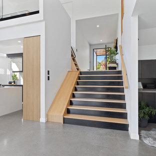 Modelo de escalera en U, contemporánea, grande, con escalones de madera, contrahuellas de madera pintada y barandilla de madera