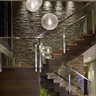 トロントの大きい木のコンテンポラリースタイルのおしゃれな折り返し階段 (木の蹴込み板、ガラスの手すり) の写真