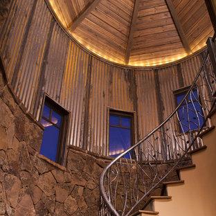 Imagen de escalera curva, rural, de tamaño medio, con escalones de madera y barandilla de metal