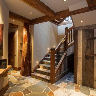 На фото: угловая лестница в стиле рустика с ступенями из сланца, подступенками из сланца и перилами из смешанных материалов с