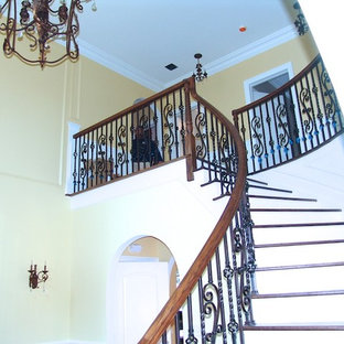 Example of a large classic painted curved mixed material railing staircase design in New York with painted risers
