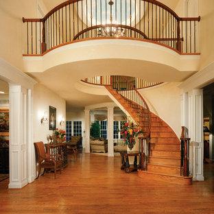 Foto de escalera curva, tradicional, de tamaño medio, con escalones de madera, contrahuellas de madera y barandilla de madera