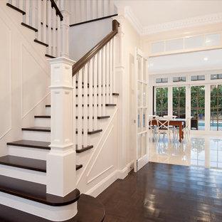 Foto de escalera en L, tradicional, extra grande, con escalones de madera, contrahuellas de madera y barandilla de madera