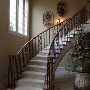 Bild på en stor vintage svängd trappa i trä, med sättsteg i målat trä och räcke i metall