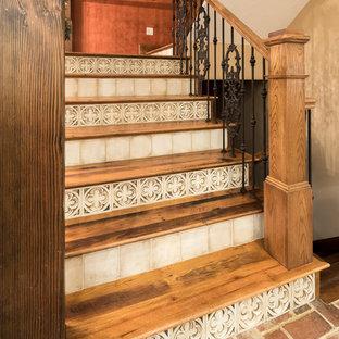 Modelo de escalera en U, ecléctica, con escalones de madera, contrahuellas con baldosas y/o azulejos y barandilla de varios materiales