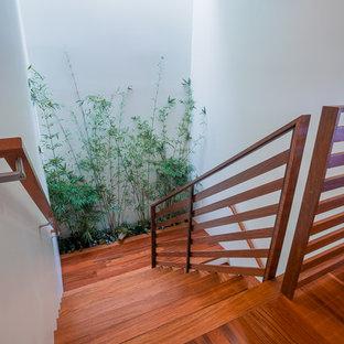 """Idee per una scala a """"U"""" tropicale di medie dimensioni con pedata in legno, alzata in legno verniciato e parapetto in legno"""