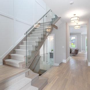 トロントの中くらいの木のトランジショナルスタイルのおしゃれな折り返し階段 (ガラスの手すり、木の蹴込み板、パネル壁) の写真