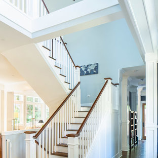 Large elegant wooden u-shaped wood railing staircase photo in Seattle with painted risers