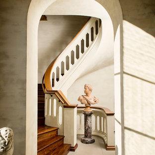 Esempio di una grande scala a chiocciola mediterranea con pedata in legno e alzata in legno