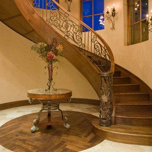 На фото: огромная изогнутая лестница в средиземноморском стиле с деревянными ступенями, деревянными подступенками и перилами из смешанных материалов с