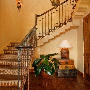 他の地域の大きい木の地中海スタイルのおしゃれなかね折れ階段 (タイルの蹴込み板、混合材の手すり) の写真