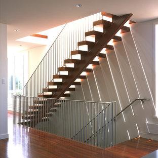 Immagine di una scala a rampa dritta moderna con pedata in legno e nessuna alzata