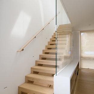 Esempio di una scala a rampa dritta minimalista di medie dimensioni con pedata in legno, nessuna alzata e parapetto in legno