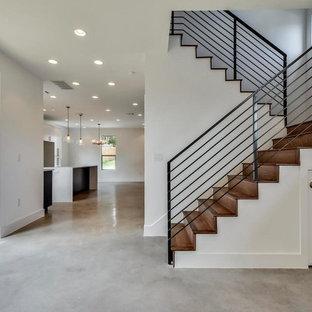 Cette photo montre un grand escalier moderne en U avec des marches en bois, des contremarches en bois et un garde-corps en métal.
