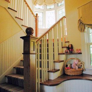 ポートランド(メイン)の中サイズの木のラスティックスタイルのおしゃれな折り返し階段 (フローリングの蹴込み板) の写真