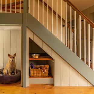 Diseño de escalera en U, de estilo de casa de campo, de tamaño medio, con barandilla de madera, escalones de madera y contrahuellas de madera pintada